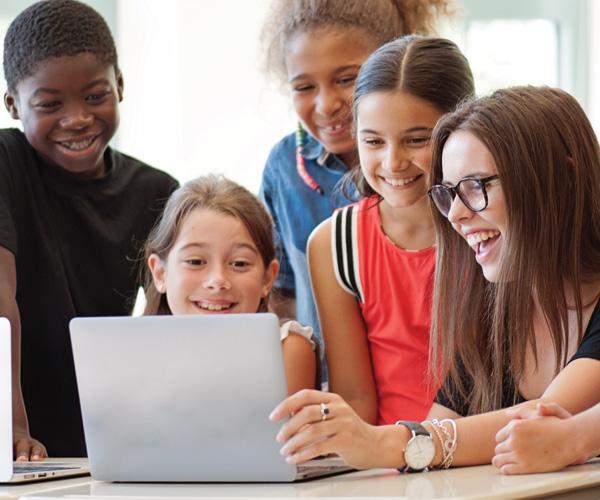 children and teacher using a laptop