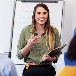 Female educator enthusiastically presenting in a learning environment