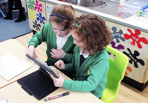Two young girls in uniform using iPad to learn