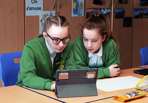 Two school girls in uniform using the iPad to collaborate