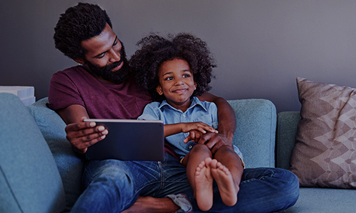 Parent and child using mobile device at home