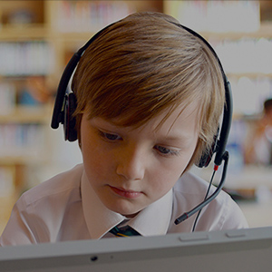 Young male student using headset in classroom